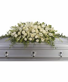 Casket spray of white roses, orchids, calla lilies and hydrangea with greenery.