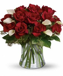One dozen red roses and six mini white calla lilies with assorted greenery in a clear glass vase.