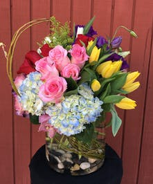 Yellow tulips, pink roses, blue hydrangea, white tulips and purple lisianthus in a clear glass vase.