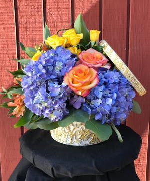 Blue hydrangea, orange and yellow roses, and orange alstroemeria in a compact box arrangement.