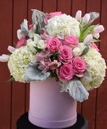 Pink box filled with pink roses, white hydrangea, white mini roses, pink tulips, pink alstroemeria and greenery.