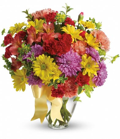 Red, yellow and purple flowers and greenery in a clear glass vase tied with yellow ribbon.