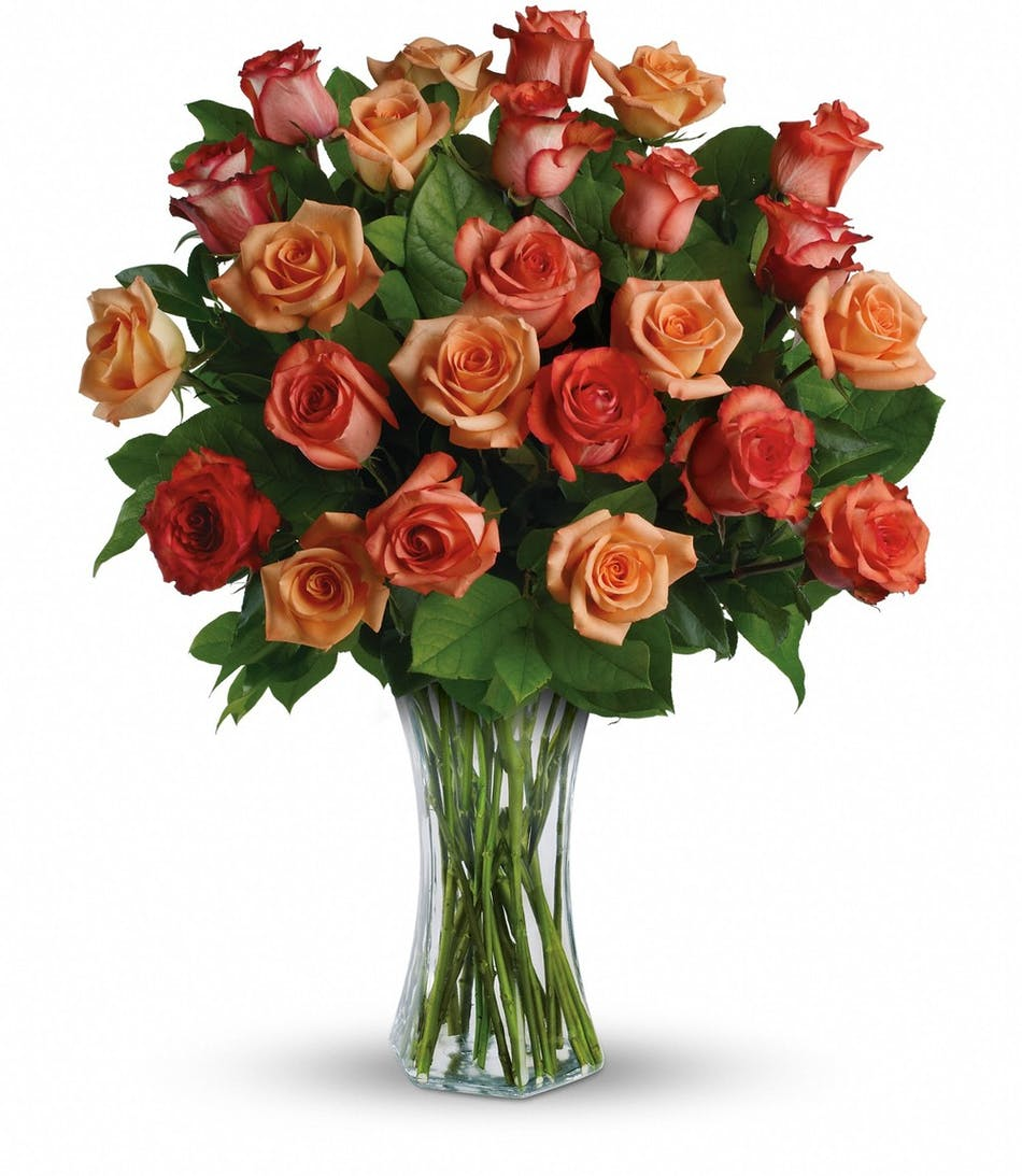 Roses in shades of orange in a clear glass vase.