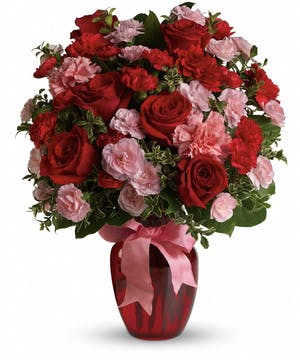 A mix of carnations and roses in shades of red and light pink in a red glass vase with pink ribbon.