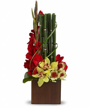 Bamboo container with yellow cymbidium orchids, red gladioli, lily grass and tropical greens.