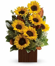 Sunflower arrangement in a wooden block vase.