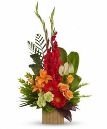 Bamboo cube container of orange and red flowers with assorted greenery.