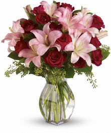 Red roses, red spray roses, and pink lilies in a clear glass vase.