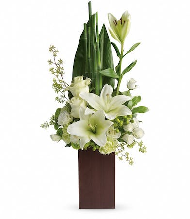 Tall bamboo vase filled with white flowers and fresh greenery.