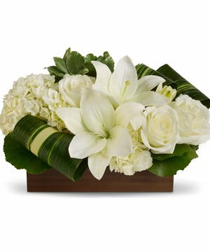Bamboo container of white hydrangea, roses and lilies with greenery.