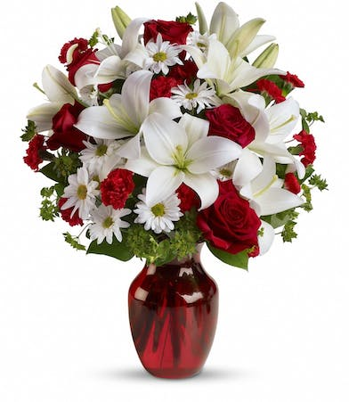 Red roses, white lilies and greenery in a ruby red vase.