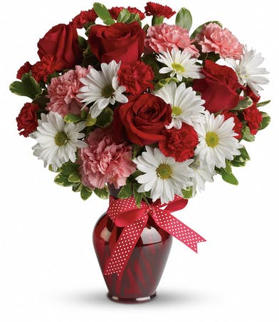Red, white and pink flowers in a red glass vase tied with a red polka dot ribbon.