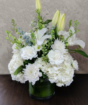 White hydrangea, cremones, carnations, larkspur, mums and stargazer lilies in a leaf-lined glass vase.