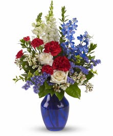 Red, white and blue patriotic flower arrangement in a blue glass vase.