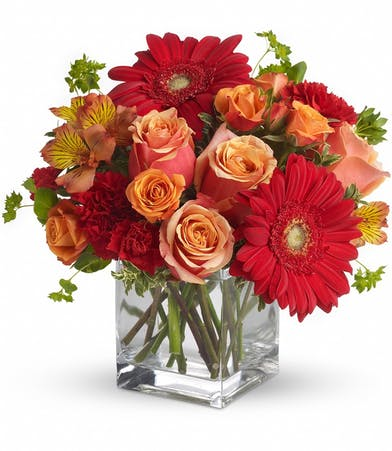 Orange and red flowers in a clear glass cube vase