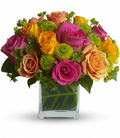 Orange and pink roses and greenery in a glass cube vase.