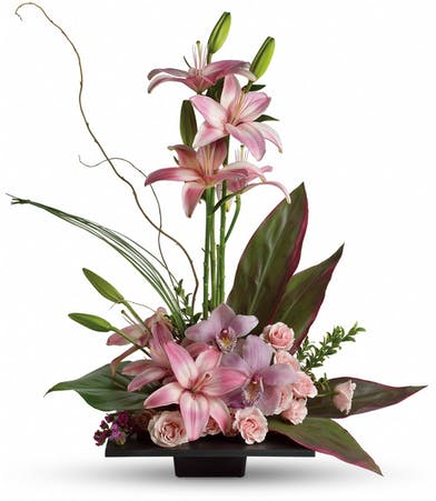 Topiary of lilies, roses and orchids accented with ti leaves.
