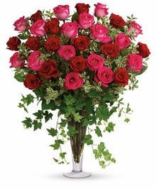 Pink and red roses with greenery in a tall glass vase.