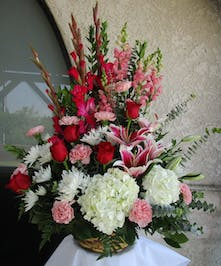 Basket of hydrangea, roses, gladiolus, snapdragos and carnations with stargazer lilies.