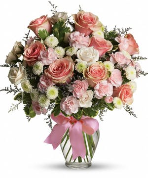 Pink and white flowers arranged in a clear glass vase with pink ribbon tied around.