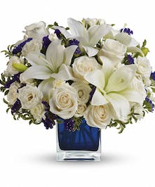 All-white flower arrangement accented with purple stacie in a blue glass cube vase.
