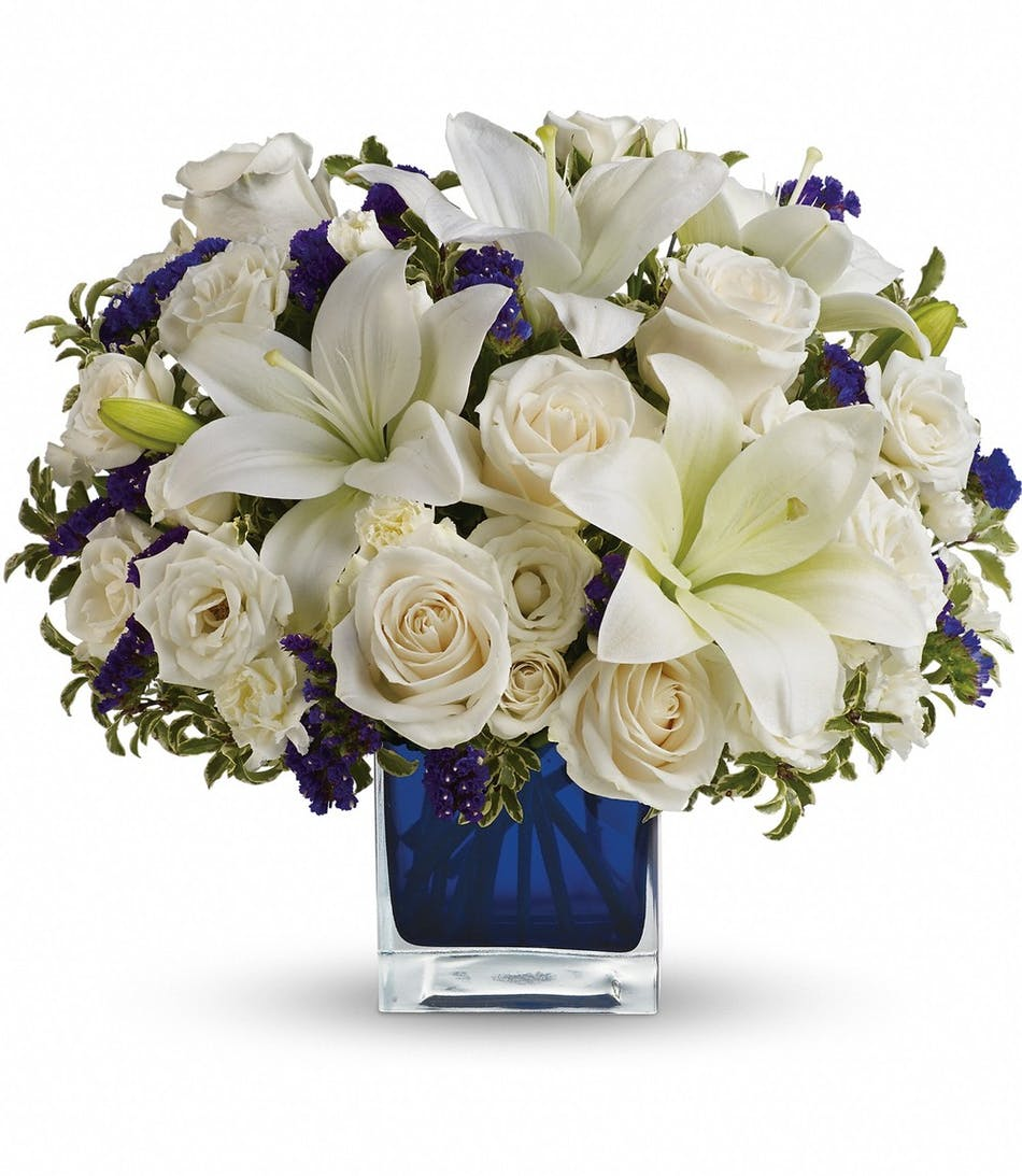 Whittier rowland heights glendora flower delivery sapphire skies all white flower arrangement accented with purple stacie in a blue glass cube vase mightylinksfo
