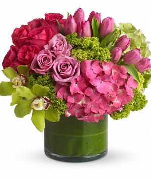 Pink and green flower arrangement in a green cylinder vase.