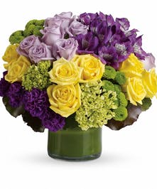 Yellow, purple and green flowers in a green cylinder vase.