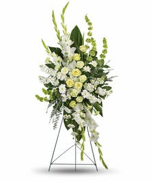 Green roses and carnations and white gladioli in a funeral flower spray arrangement.