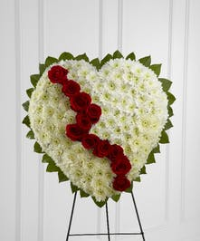 Broken heart funeral tribute of white chrysanthemums, red roses and greenery.