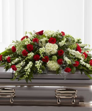 Casket spray of red and white flowers with greenery.