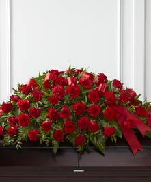 Casket spray of red roses and carnations with greenery and a red satin ribbon.