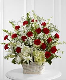 Sympathy basket of red roses, Queen Anne's lace and white hydrangea and lilies.