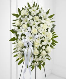 White roses and other flowers and greenery in a funeral spray arrangement.