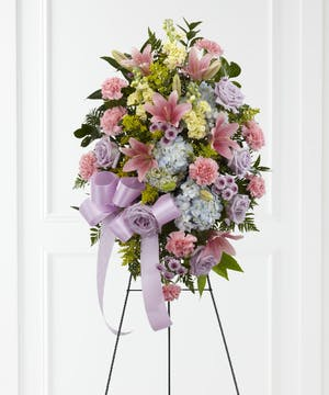 Sympathy spray of pastel pink, blue and green flowers presented on an easel with a lavender ribbon.