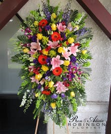 Sympathy spray of yellow roses, pink lilies, purple orchids, orange daisies and more.
