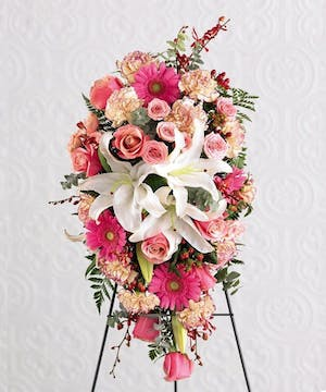 Sympathy spray of bright pink, light pink and white flowers with greenery.