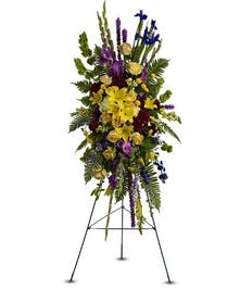 Sympathy spray of yellow, green and purple flowers with greenery.