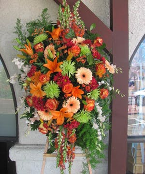 Sympathy spray of bright green and orange flowers presented on a wooden stand.