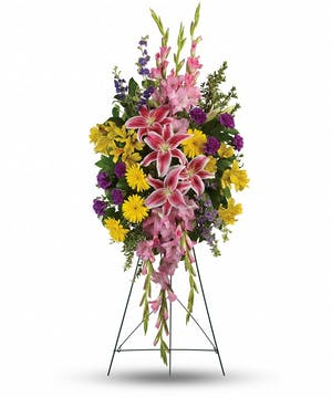Sympathy spray of pink, purple and yellow flowers with assorted greenery.