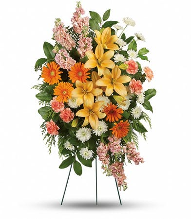 Orange, peach and yellow standing funeral spray arrangement.