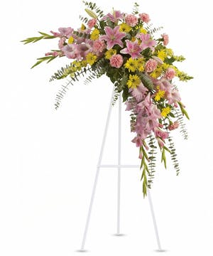 Sympathy spray of pink and yellow flowers accented with greenery.