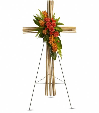 Orange flowers and greenery on a cross fashioned out of natural river cane. Standing spray for a funeral.