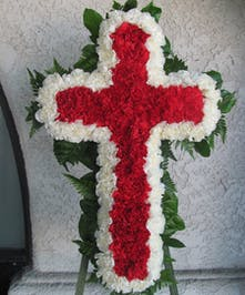 Cross of red and white carnations for a funeral service.