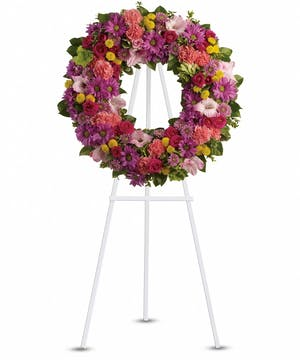 Sympathy wreath of green, hot pink and pink flowers presented on an easel.