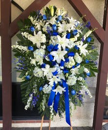 Sympathy spray of blue and white flowers and greenery accented with a blue ribbon.