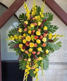 Sympathy spray of bright yellow roses, gladiola, orange carnations and more.