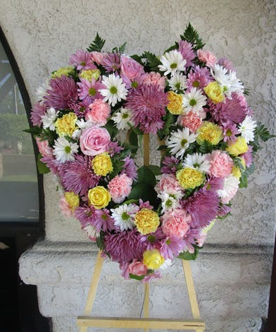 Purple, yellow and pink flowers made into a heart-shaped funeral wreath on a standing easel.
