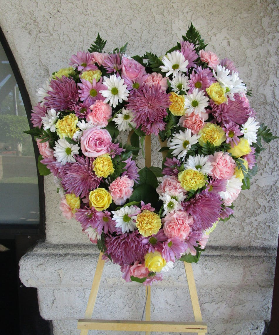 Rowland heights funeral flowers lovely thoughts funeral heart purple yellow and pink flowers made into a heart shaped funeral wreath on a izmirmasajfo
