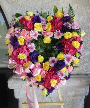 Sympathy heart of bright pink, yellow and purple flowers with a pink bow.